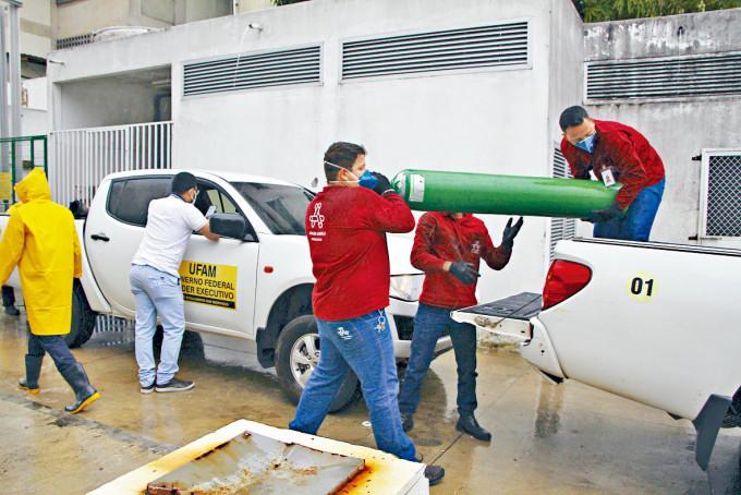 亞馬遜州瑪瑙斯市一所醫院的職員抬走空的氧氣樽。