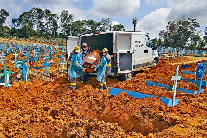 在亞馬遜州首府瑪瑙斯,墳場工人將一名因新冠肺炎死亡的長者下葬。