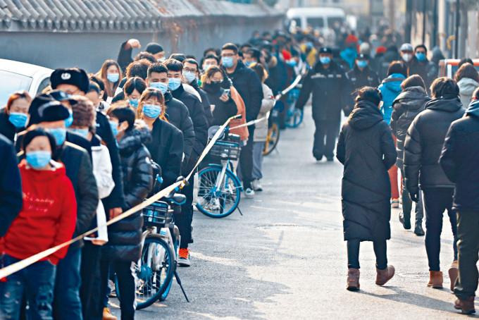 北京市民昨天大排長龍接受病毒檢測。
