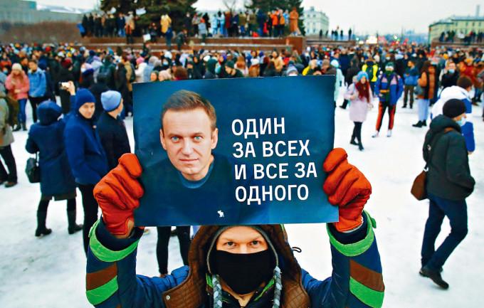 示威者在聖彼得堡,舉起印有納瓦爾尼肖像的海報。