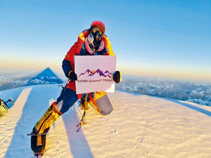 攀山隊員謝爾帕上周六手持隊旗在K2峰頂拍照。