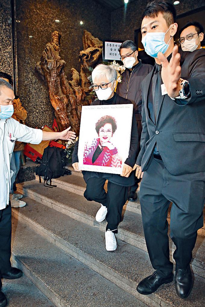 蕭紫筠手捧母親琴姐遺照步上靈車。