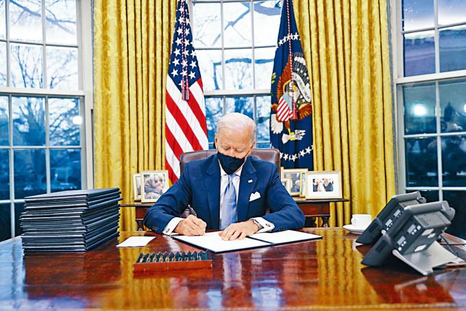 拜登周三在白宮橢圓形辦公室簽署行政命令。