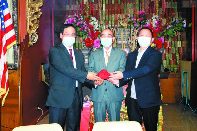 在元老惠喜(中)主持監交下,連任主席榮達(右)、副主席健賢(左)接過印信,履新就職,為黃氏宗親總會掌舵。馬紅兵攝