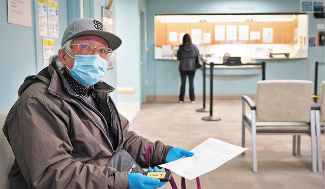 高建武在東華醫院拿著輪候牌,等待「雙陰」檢測。         記者黃偉江攝