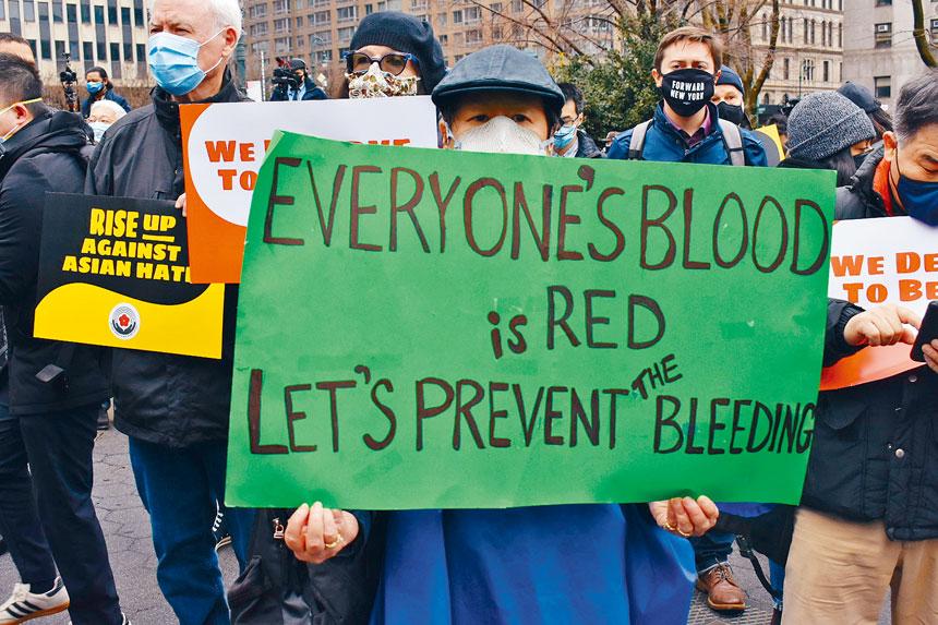 民眾手持「每個人的血液都是紅色的。讓我們一起阻止再流血」的標語。