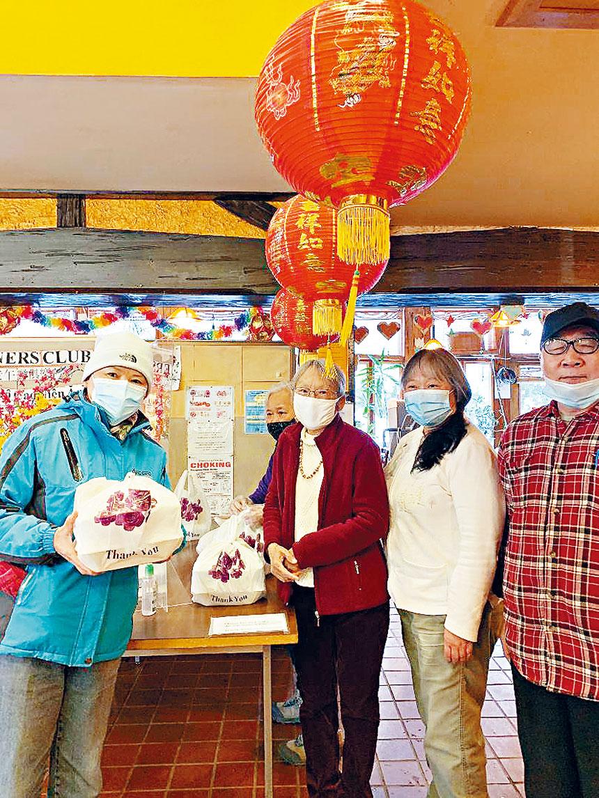 東南亞中心舉行春節午餐會,鄔亮珊(左2)、義工們與領取盒飯的僑胞(左1)。梁敏育攝