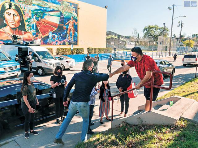 州長紐森表示更多疫苗將運往加州廣闊的中谷農業地區。圖為紐森(左)周日到訪洛杉磯Ramona Gardens康樂中心與居民Israel Ortiz擊肘問候。美聯社