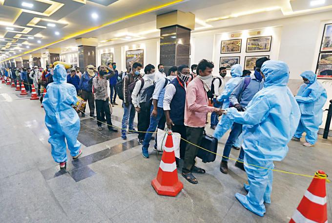 在孟買火車站,乘客周一上車前量體溫。