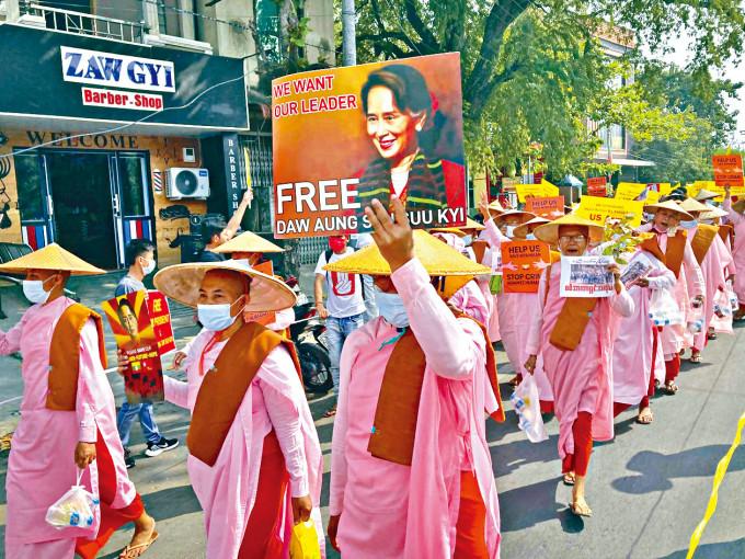 緬甸尼姑周五在曼德勒高舉標語牌遊行,要求釋放昂山素姬。