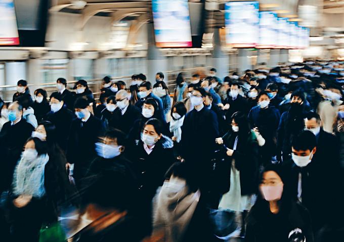 東京人在品川站戴口罩上下班。