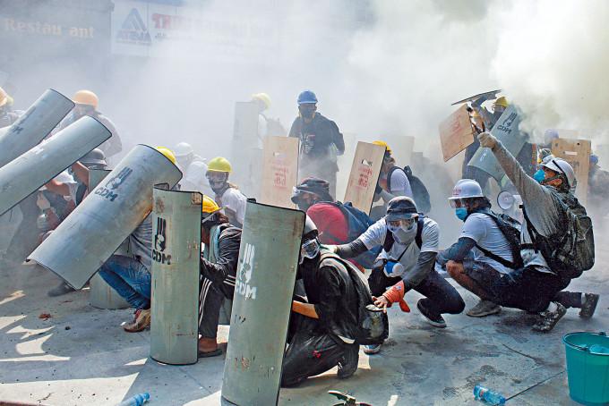 仰光防暴警察向示威者發射催淚彈和閃光彈,示威者以盾牌躲避。