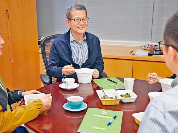 陳茂波昨於網誌上載一張與同事吃外賣飯盒的照片,桌上放有兩份封面草綠色的《財政預算案》。
