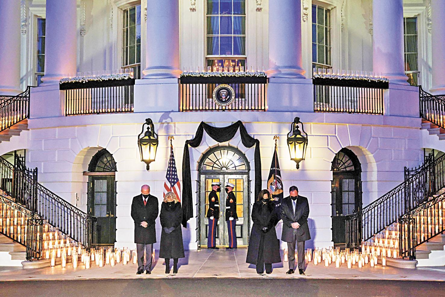 拜登與第一夫人吉爾、副總統賀錦麗及其丈夫任德龍一起,站在白宮外點燃的500枝蠟燭旁默哀。路透社