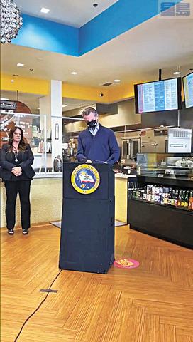 州長紐森在沙加緬度一家熟食店簽署總額達76億元的救助計劃。州長辦公室