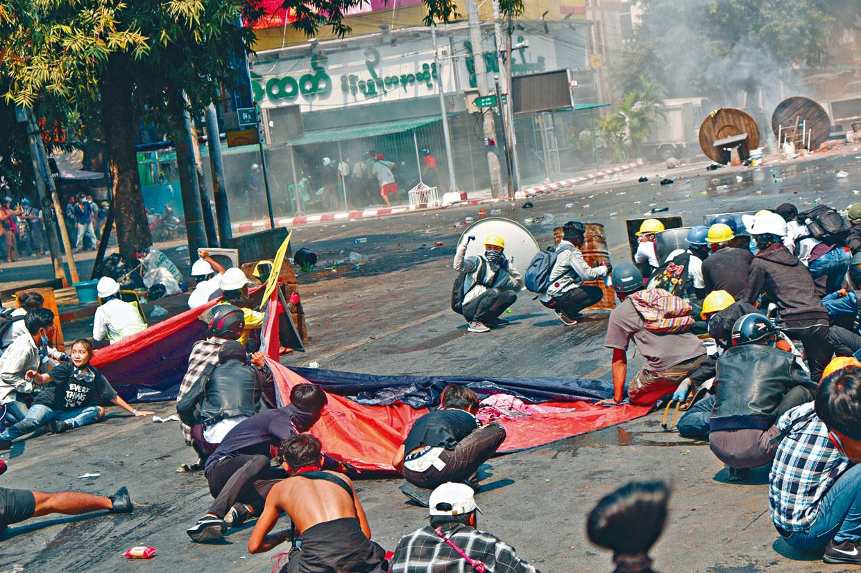 緬甸曼德勒的示威者蹲在地上躲避警方的槍擊。路透社