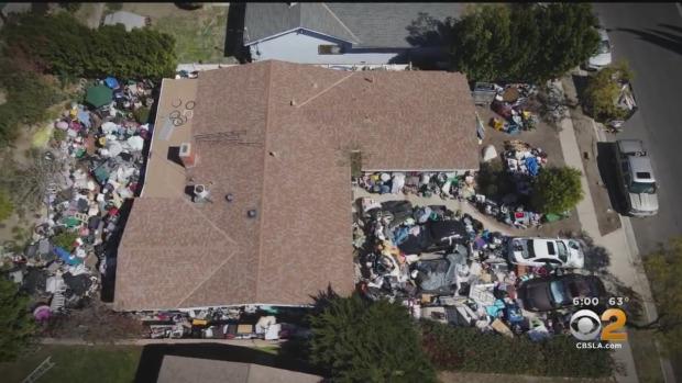 洛杉磯一處民宅垃圾堆積如山,讓附近鄰居十分困擾。CBSLA新聞畫面