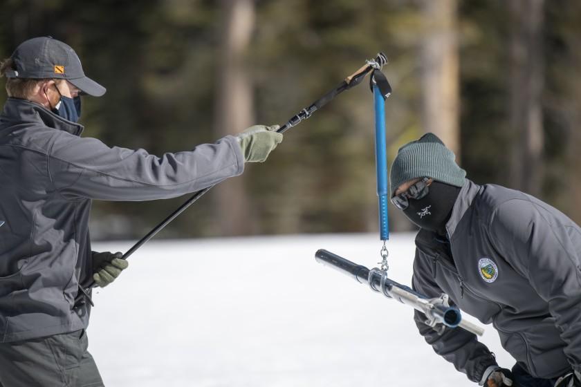 氣象觀測人員正在檢測積雪量。加州政府水資源部