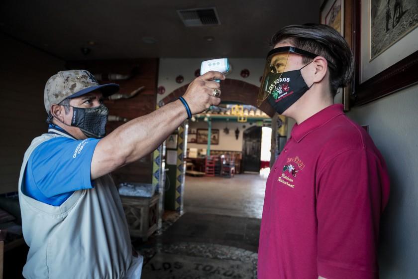 墨西哥餐廳老闆Nicolas Montano替員工測量體溫。洛杉磯時報