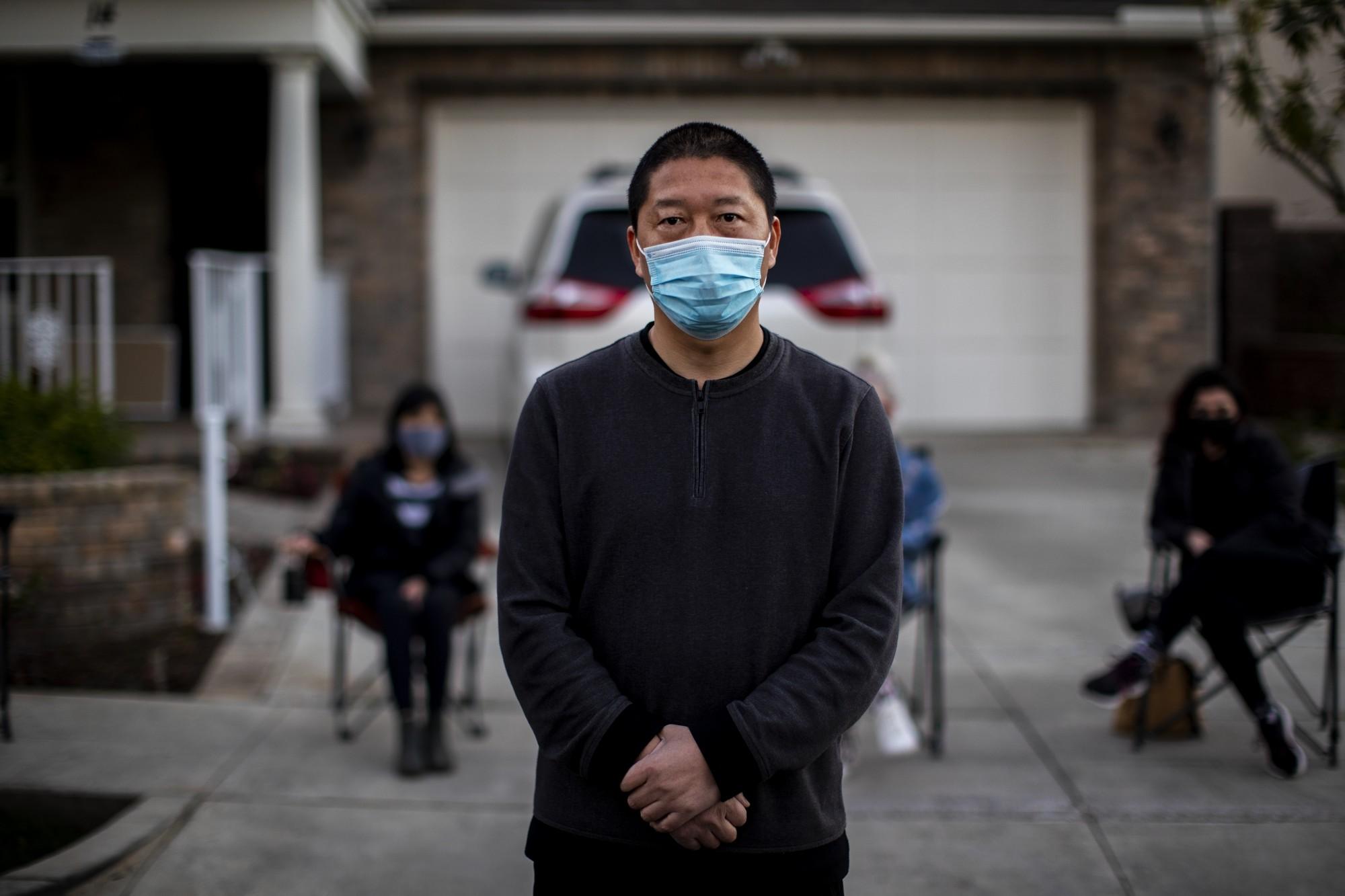 司海君站在家門前,後面為由鄰居們所組成的夜間守衛隊。洛杉磯時報