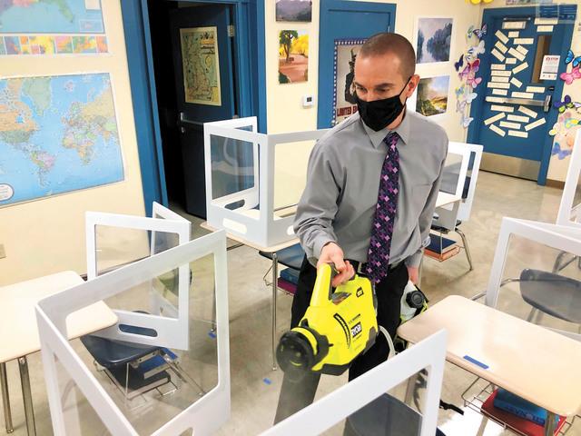 加州再有六縣疫情趨緩獲降級。圖為一家獲准開學面授課程的學校校長在消毒課桌。美聯社