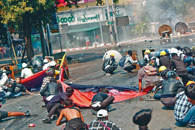 曼德勒的示威者蹲在地上躲避警方的槍擊。