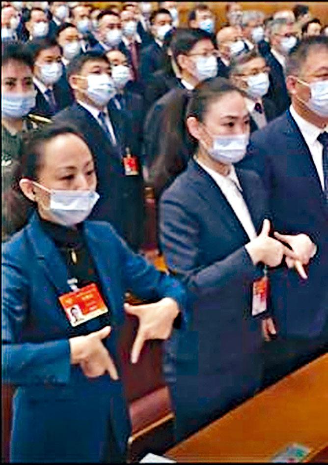 邰麗華(前)與另一委員以手語「唱」國歌。