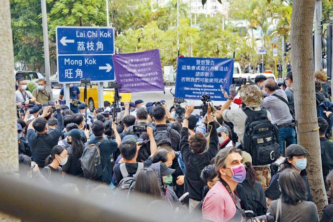 警方向法院大樓外人群高舉藍旗、紫旗,警告非法集結及違反國安法。