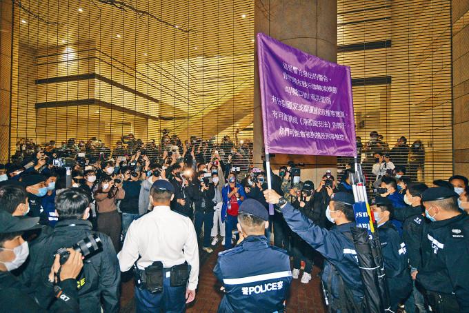 約百人在法院外圍聚集叫囂,警方外舉起紫旗。