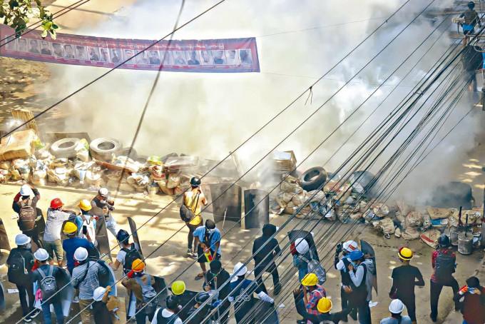示威者昨日在仰光冒着催淚氣抗議。