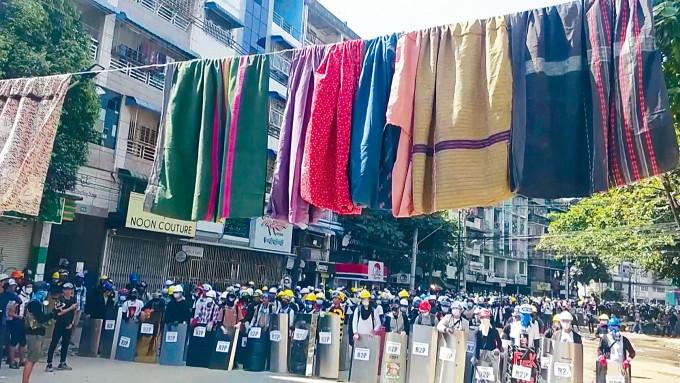 在仰光一個示威地點,昨日可見持盾牌的示威者前面,掛起傳統女性筒裙。