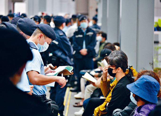 警方票控在法院外排隊等候的市民違反限聚令。