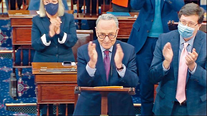 參議院多數黨領袖舒默(中)上周六在紓困案表決前,帶頭鼓掌。