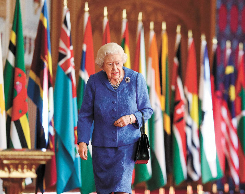 英女王預錄的演說聲音搭配她在聖喬治禮拜堂兩排英聯邦旗幟中漫步的畫面。   美聯社