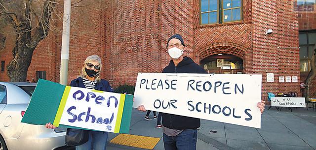 兩名家長在羅斯福中學路邊舉起「重啟學校」的橫幅。記者李兆庭攝