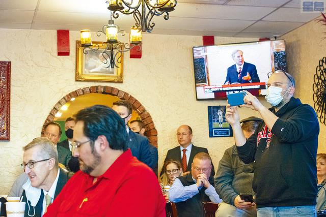 ■德州州長阿伯特2日在一家墨西哥餐廳宣布,大部分防疫措施將在10日取消。圖為電視正在直播他的講話。美聯社