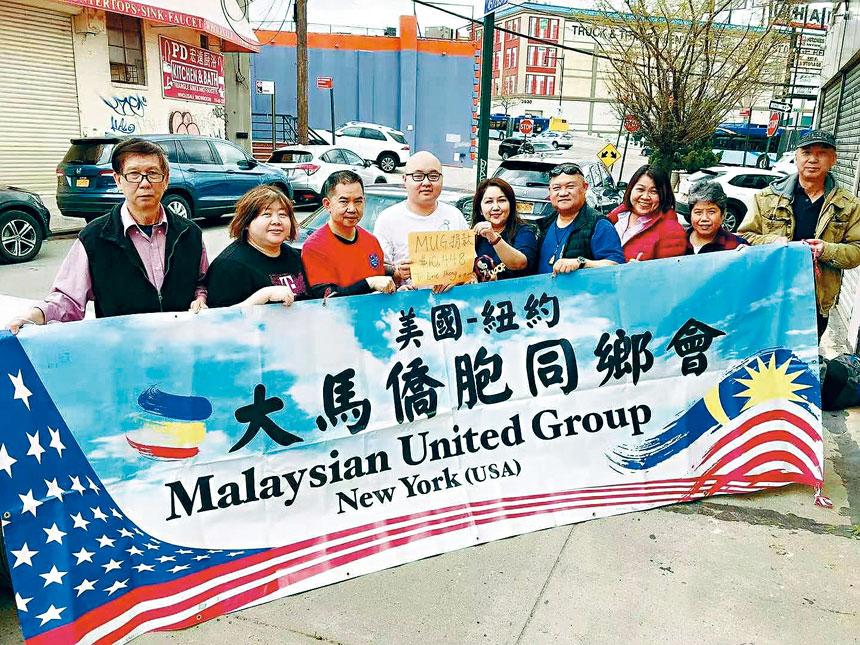 美國紐約大馬同鄉會會長朱雁影與同鄉會成員在法拉盛把善款移交給Eric Thong。