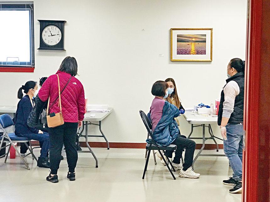 華裔社區居民在自己門口接種疫苗。溫友平攝