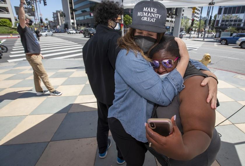 前明尼阿波利斯警察喬文被判有罪後,兩名和平示威者互相擁抱。洛杉磯時報