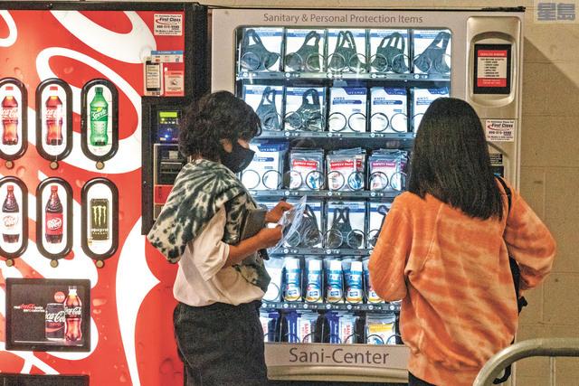 加州疫情繼續趨緩,圖為民眾在有限度恢復開放的環球影城的自動售賣機購買個人防護用品。美聯社資料圖片