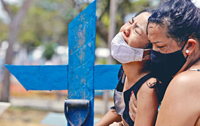 巴西一名十六歲少女因新冠疫症痛失母親,在墳前哭斷腸。
