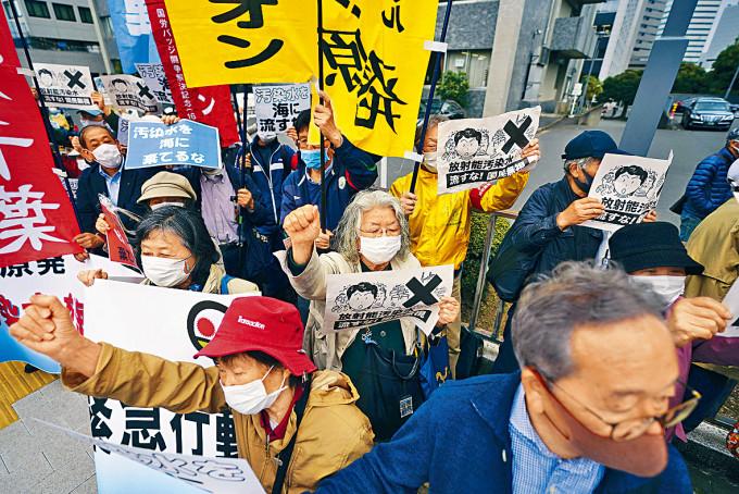 日本民眾周二在首相府外高叫口號,抗議將核廢水排入大海。