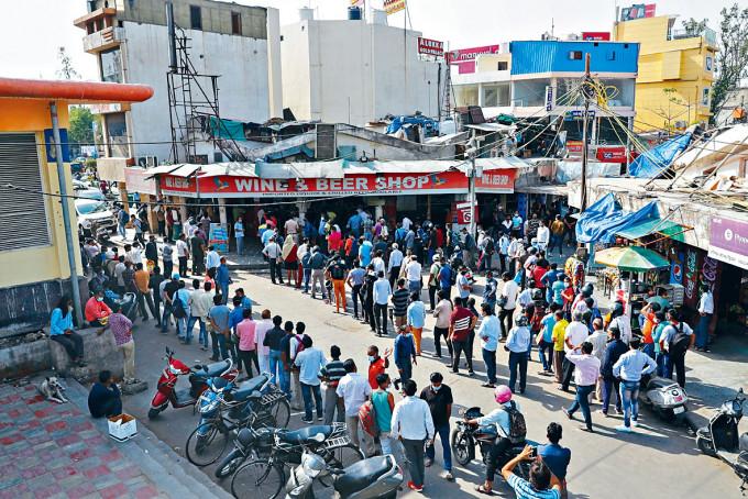 民眾周一在新德里排隊買酒。