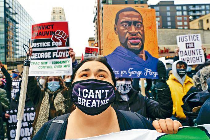 明尼阿波利斯市周一有示威者帶同被殺黑人弗洛伊德的肖像,到一間警署外抗議。美聯社