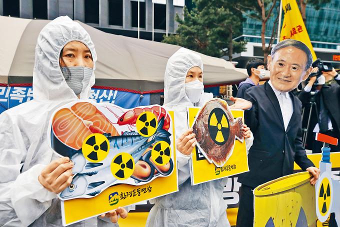 環保分子周二在首爾示威,戴上日相菅義偉的面具抗議排放核廢水。