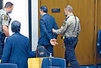 肖萬(中)被判罪成後被庭警鎖上手扣帶離法庭。