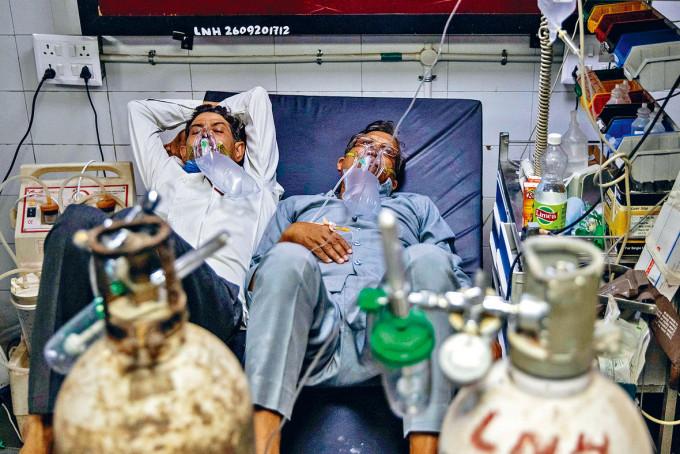 首都新德里病牀短缺,有確診病人須二人同卧一牀。