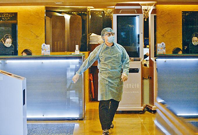 華美達華麗酒店三名住客確診,部分職員穿上保護衣工作。