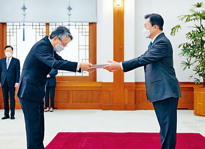 文在寅(右)昨日在首爾從日本大使相星孝一手中接過國書。