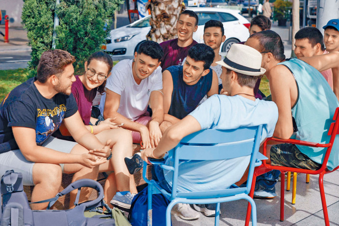 一群青年沒戴口罩,在特拉維夫街頭聚談。